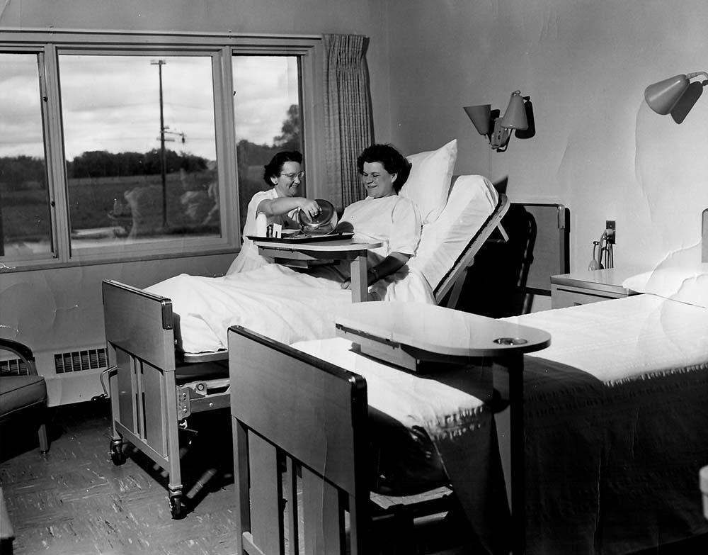 Nurse Maurita Jahnz serving a meal, 1954